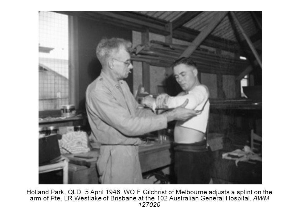 Holland Park, QLD. 5 April 1946. WO F Gilchrist of Melbourne adjusts a splint on the arm of Pte. LR Westlake of Brisbane at the 102 Australian General