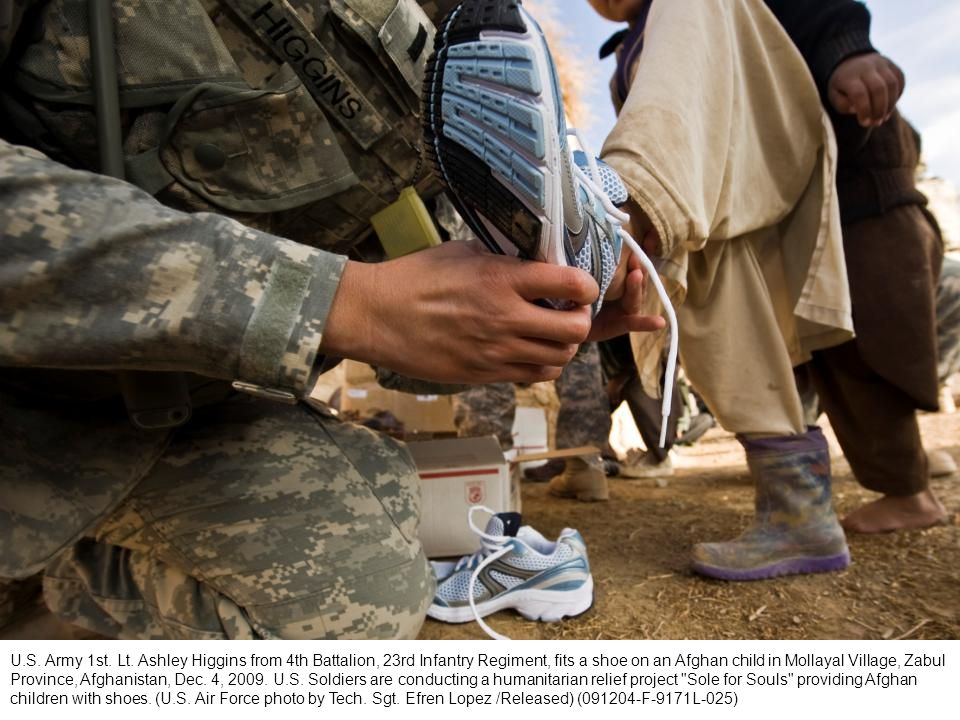 U.S. Army 1st. Lt. Ashley Higgins from 4th Battalion, 23rd Infantry Regiment, fits a shoe on an Afghan child in Mollayal Village, Zabul Province, Afgh