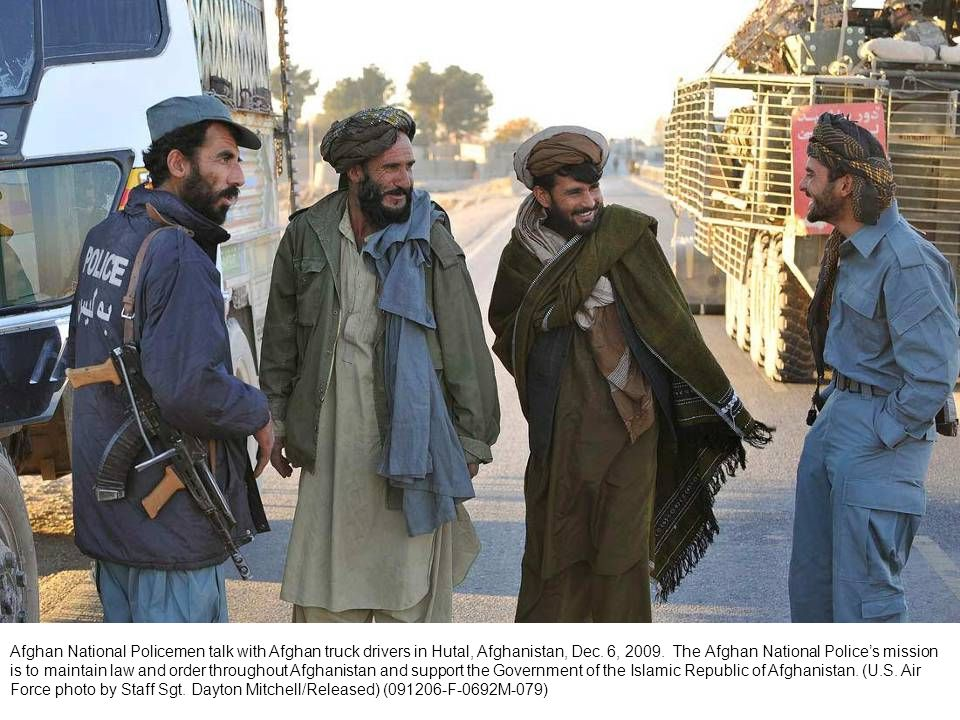Afghan National Policemen talk with Afghan truck drivers in Hutal, Afghanistan, Dec. 6, 2009. The Afghan National Polices mission is to maintain law a