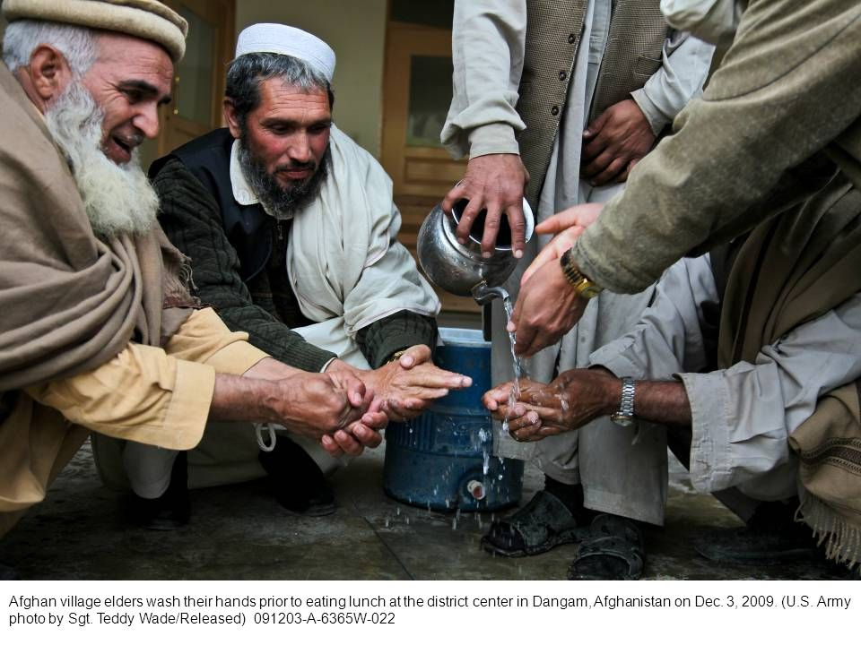 Afghan village elders wash their hands prior to eating lunch at the district center in Dangam, Afghanistan on Dec. 3, 2009. (U.S. Army photo by Sgt. T
