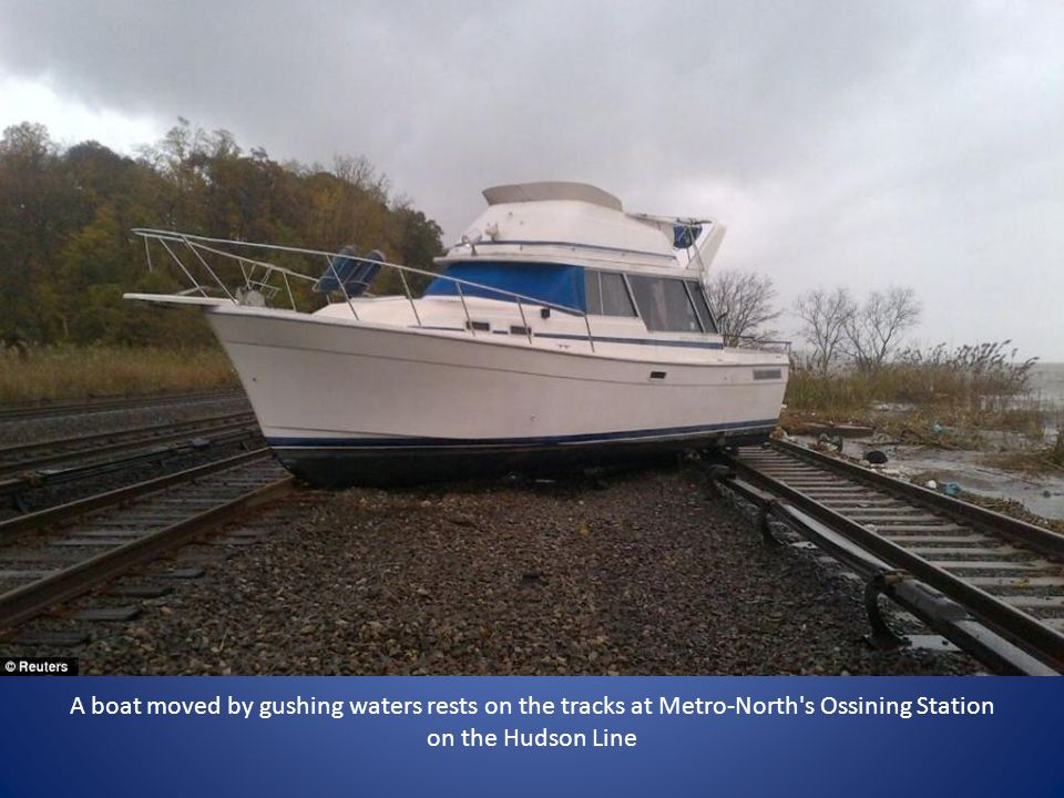 A boat moved by gushing waters rests on the tracks at Metro-North's Ossining Station on the Hudson Line