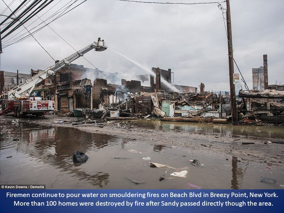 Firemen continue to pour water on smouldering fires on Beach Blvd in Breezy Point, New York. More than 100 homes were destroyed by fire after Sandy pa