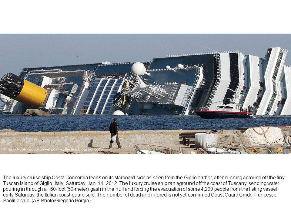The luxury cruise ship Costa Concordia lays on its side after running aground the tiny Tuscan island of Giglio, Italy, Saturday, Jan.