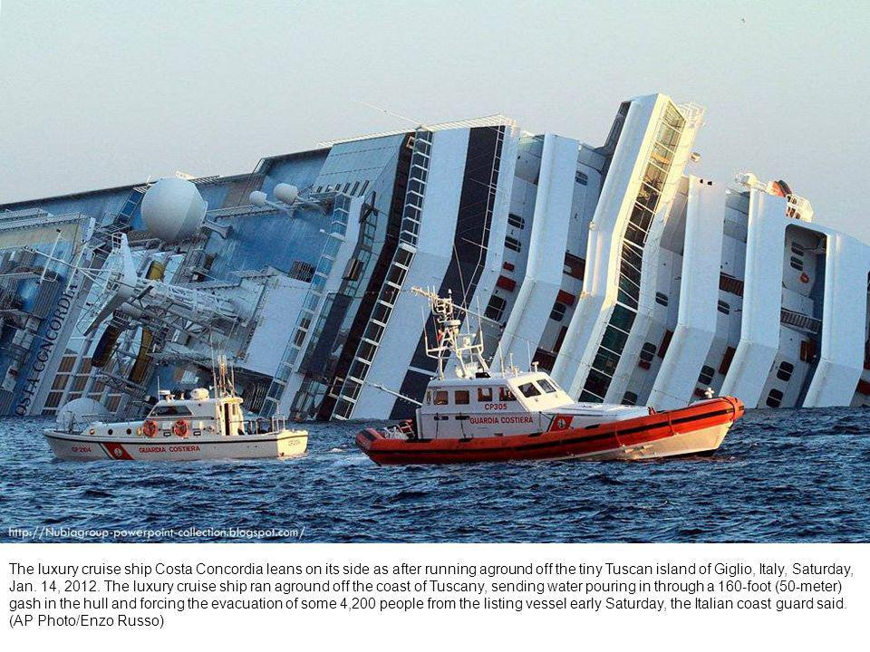 The luxury cruise ship Costa Concordia lies virtually flat, its right-hand side submerged in the water, along the coast of the tiny Tuscan island of Giglio, Italy, Saturday, Jan.