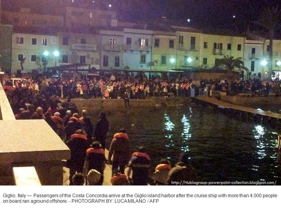 Evacuated Costa Concordia passengers wear life vests and blankets as they arrive at shore.