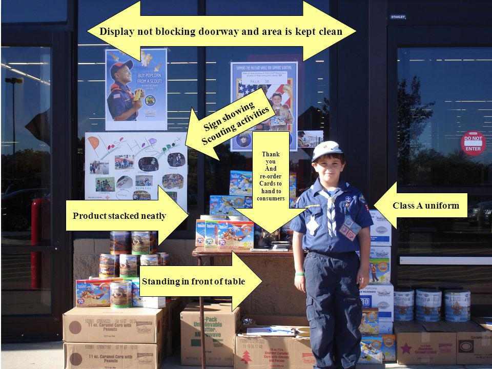 Class A uniform Standing in front of table Product stacked neatly Sign showing Scouting activities Display not blocking doorway and area is kept clean