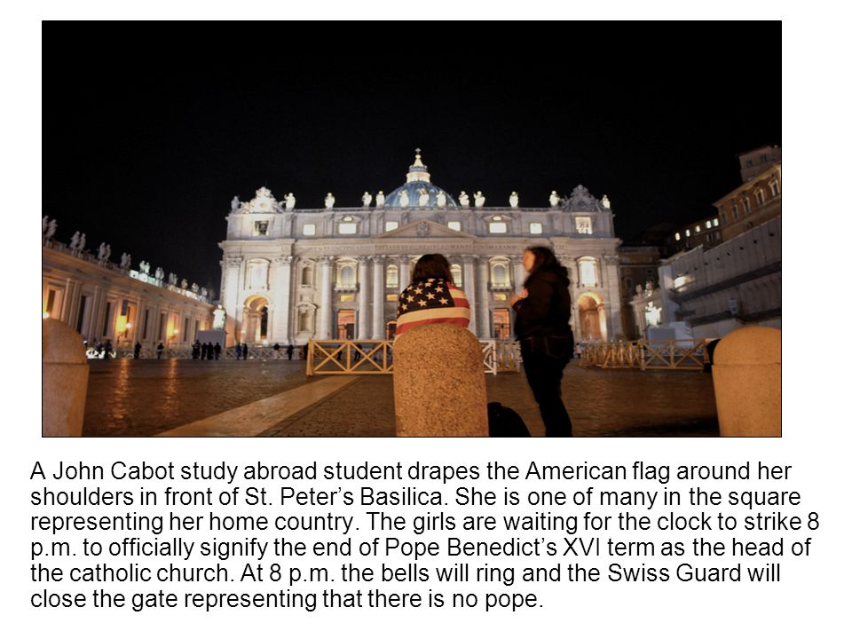 A John Cabot study abroad student drapes the American flag around her shoulders in front of St. Peters Basilica. She is one of many in the square repr