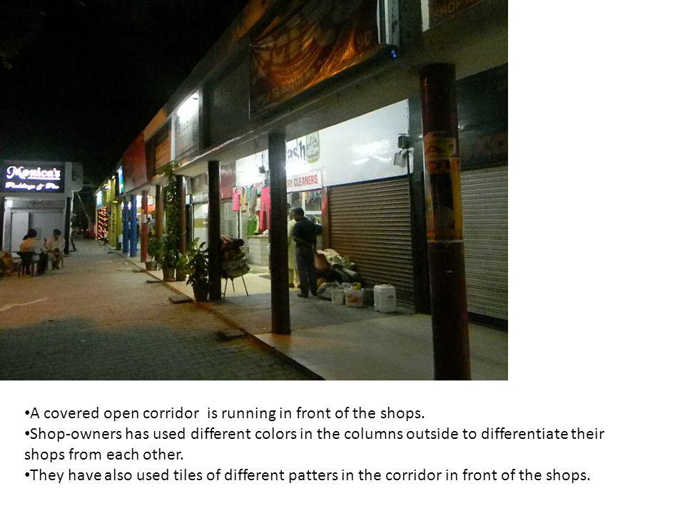 A covered open corridor is running in front of the shops.