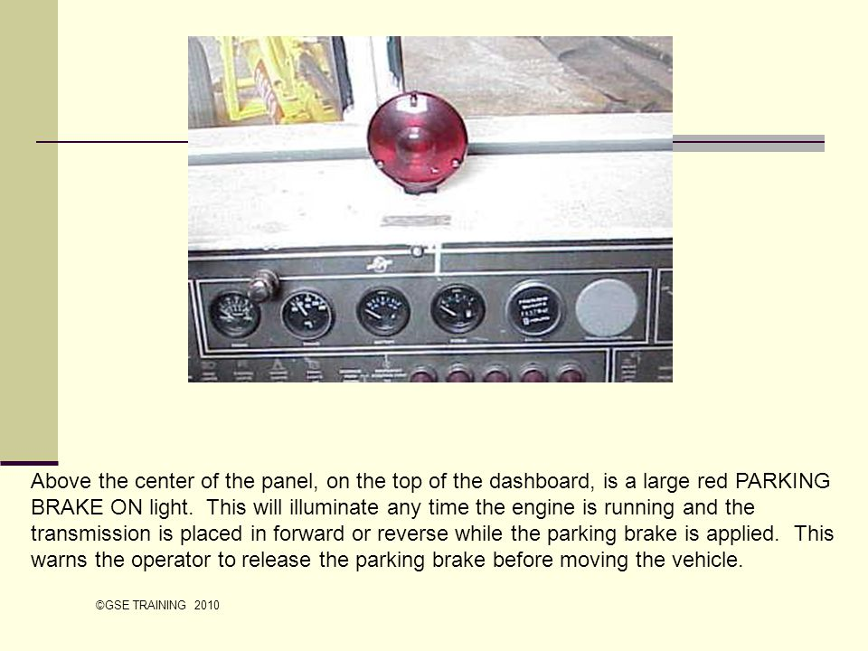 Above the center of the panel, on the top of the dashboard, is a large red PARKING BRAKE ON light. This will illuminate any time the engine is running