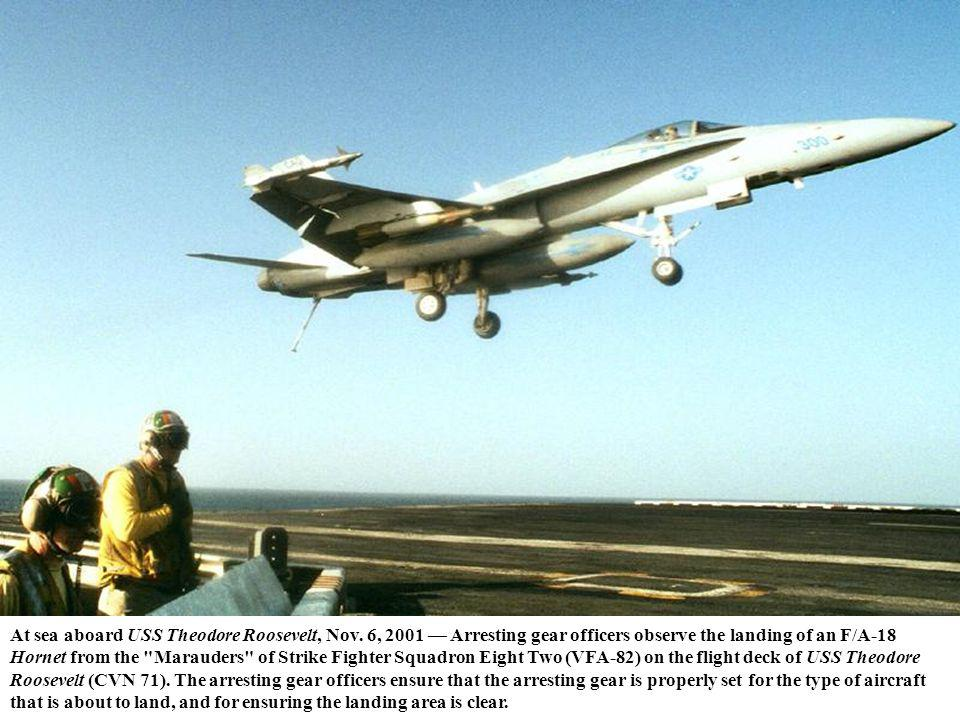 At sea aboard USS Theodore Roosevelt, Nov. 6, 2001 Arresting gear officers observe the landing of an F/A-18 Hornet from the