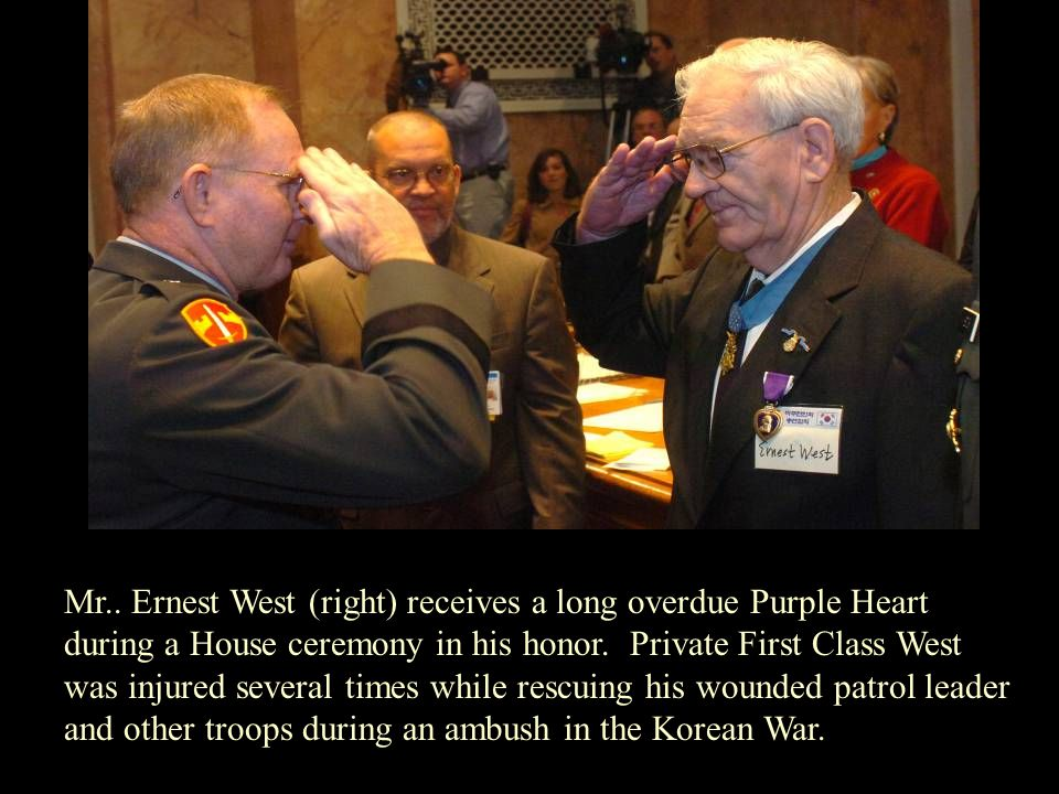 Mr.. Ernest West (right) receives a long overdue Purple Heart during a House ceremony in his honor. Private First Class West was injured several times