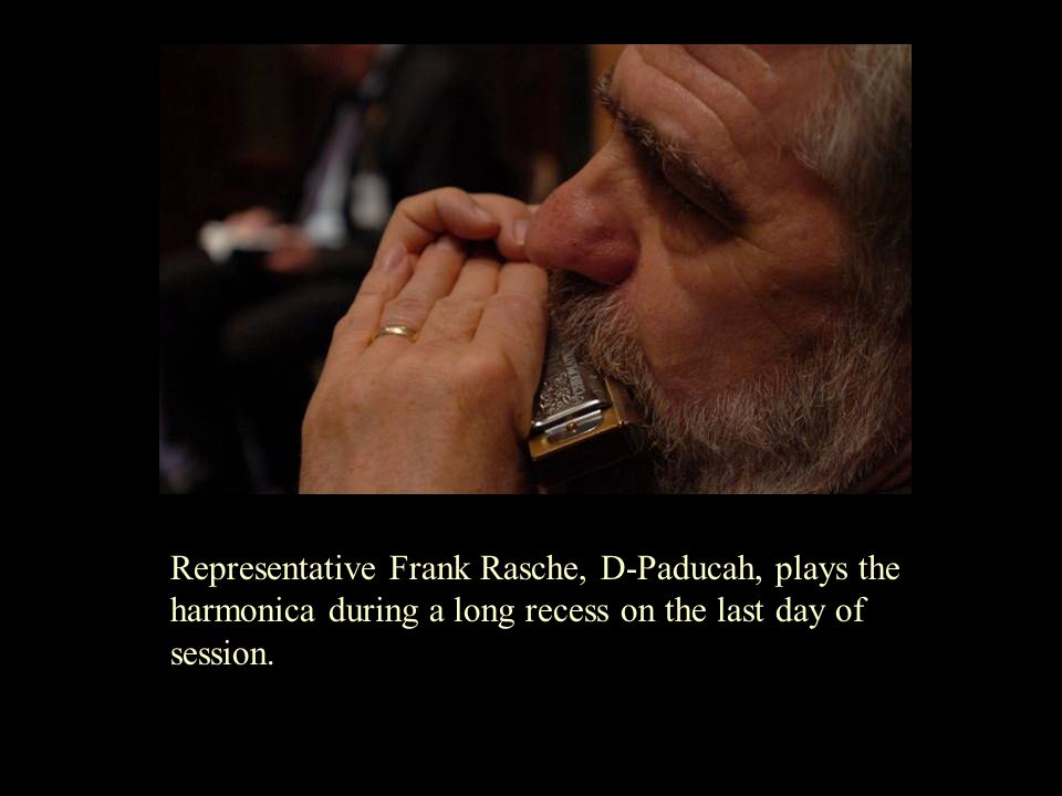 Representative Frank Rasche, D-Paducah, plays the harmonica during a long recess on the last day of session.