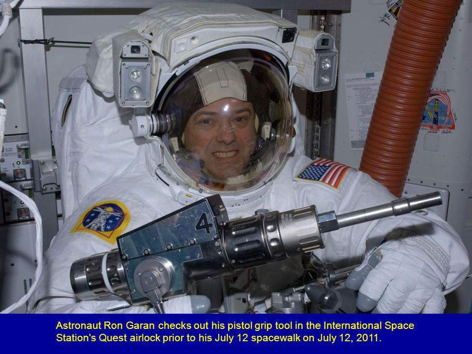 Astronaut Rex Walheim works on the mid-deck of Atlantis.
