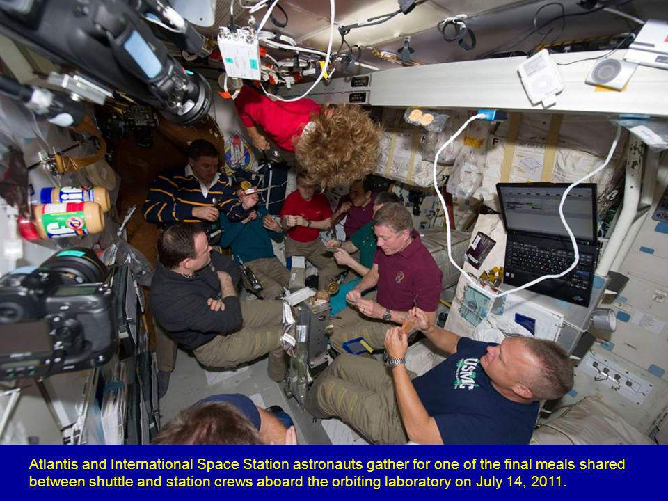 Spacewalker Ron Garan rides on the International Space Station's robotic arm with Earth below as he transfers a failed pump module to the cargo bay of