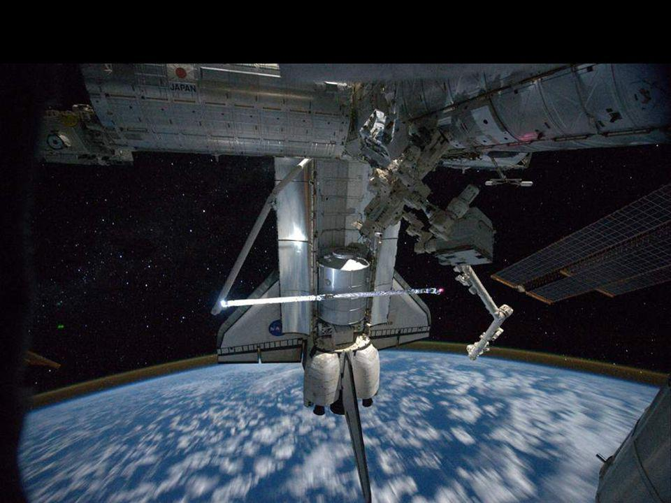 Astronaut Mike Fossum carries a Robotics Refueling Mission payload from Atlantis cargo bay to a platform used by the space station s famous robot DEXTRE.