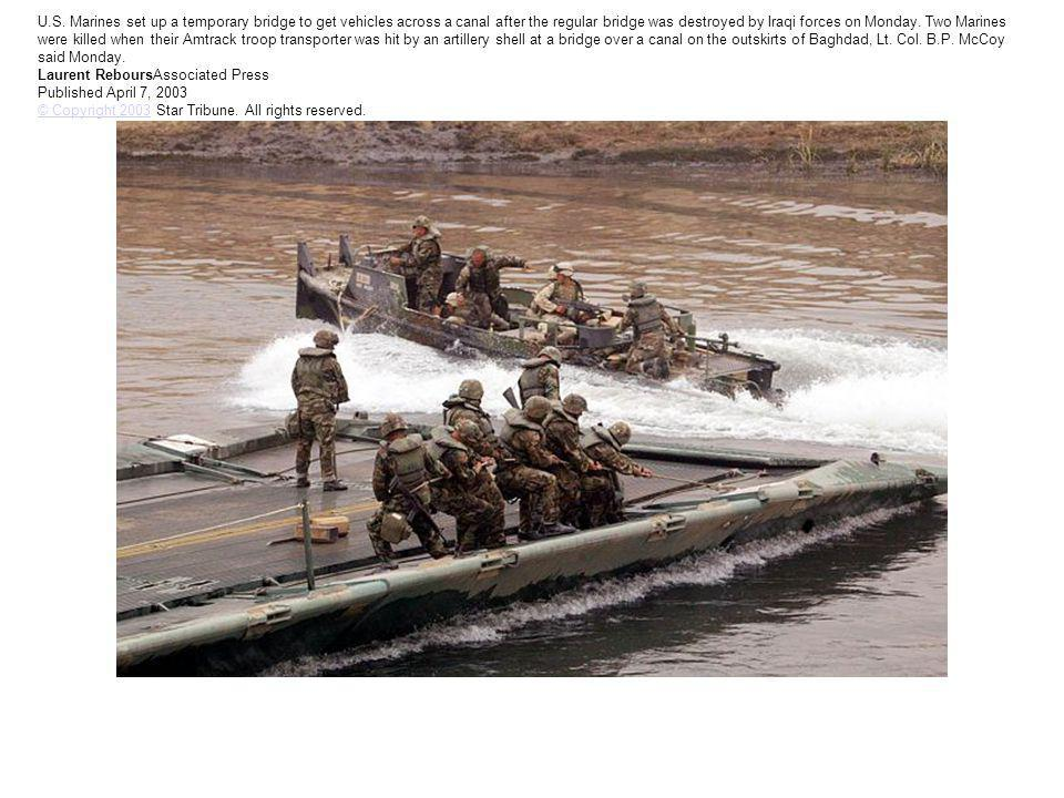 U.S. Marines set up a temporary bridge to get vehicles across a canal after the regular bridge was destroyed by Iraqi forces on Monday. Two Marines we