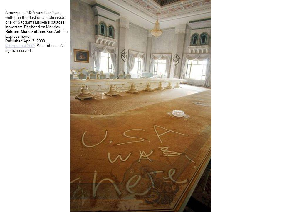 A message USA was here was written in the dust on a table inside one of Saddam Hussein s palaces in western Baghdad on Monday.