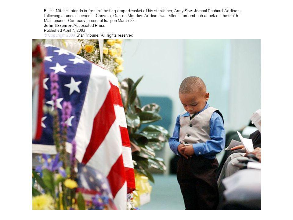 Ellijah Mitchell stands in front of the flag-draped casket of his stepfather, Army Spc. Jamaal Rashard Addison, following a funeral service in Conyers
