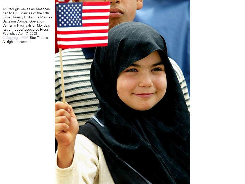 An Iraqi girl waves an American flag to U.S. Marines of the 15th Expeditionary Unit at the Marines Battalion Combat Operation Center in Nasiriyah on M