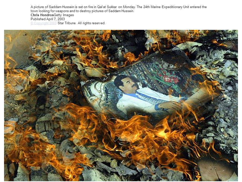 A picture of Saddam Hussein is set on fire in Qal'at Sukkar on Monday. The 24th Marine Expeditionary Unit entered the town looking for weapons and to