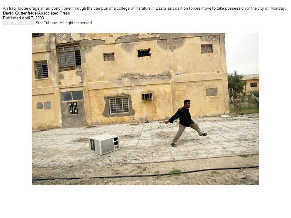 An Iraqi looter drags an air conditioner through the campus of a college of literature in Basra as coalition forces move to take possession of the cit