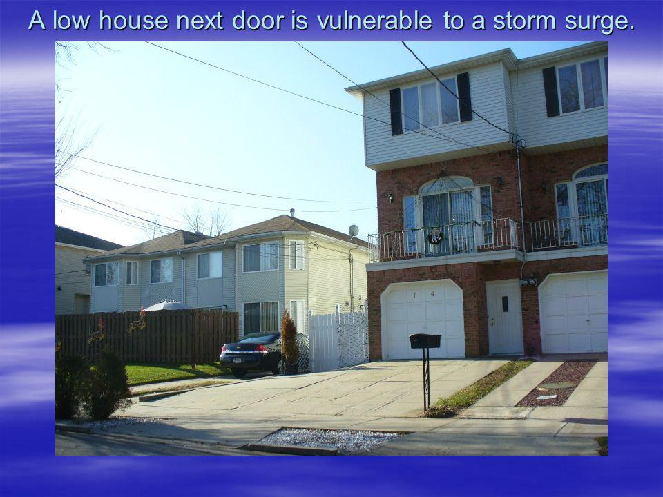 A low house next door is vulnerable to a storm surge.