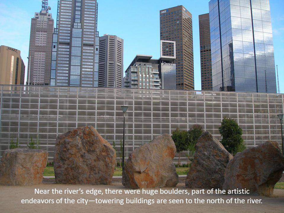 Near the rivers edge, there were huge boulders, part of the artistic endeavors of the citytowering buildings are seen to the north of the river.