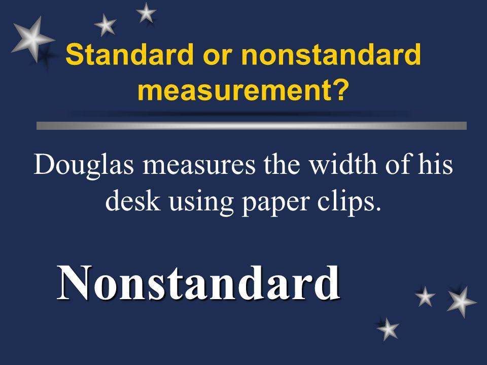 Standard or nonstandard measurement. Douglas measures the width of his desk using paper clips.