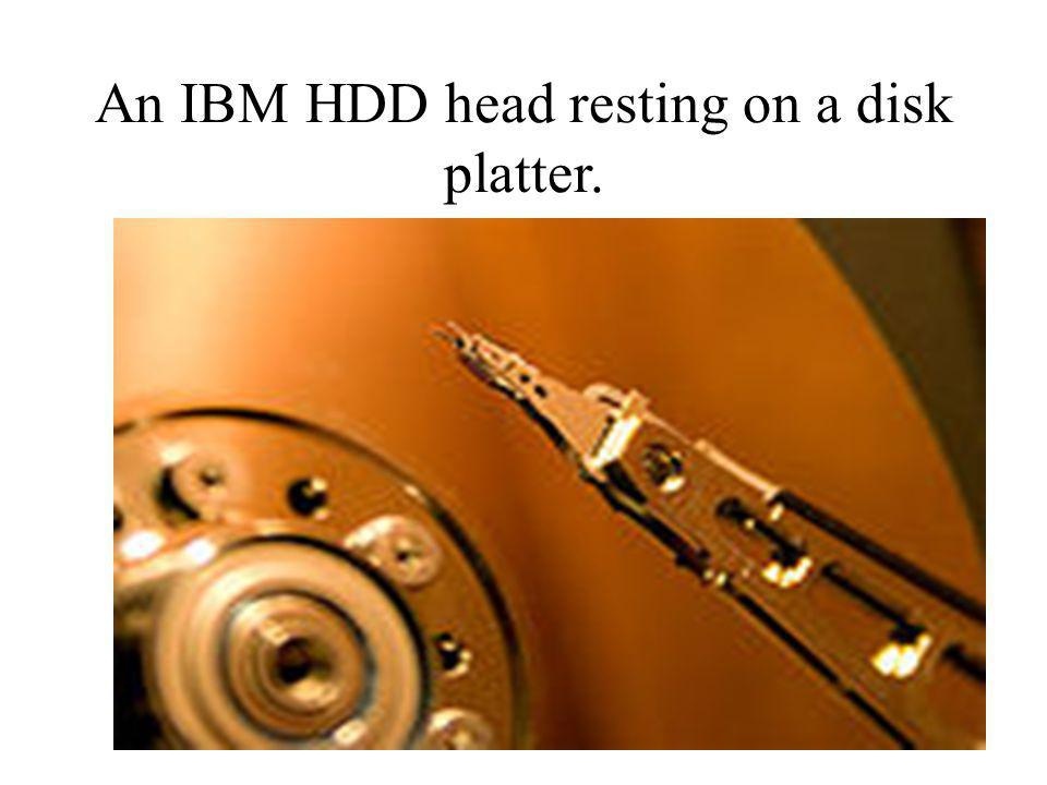 An IBM HDD head resting on a disk platter.