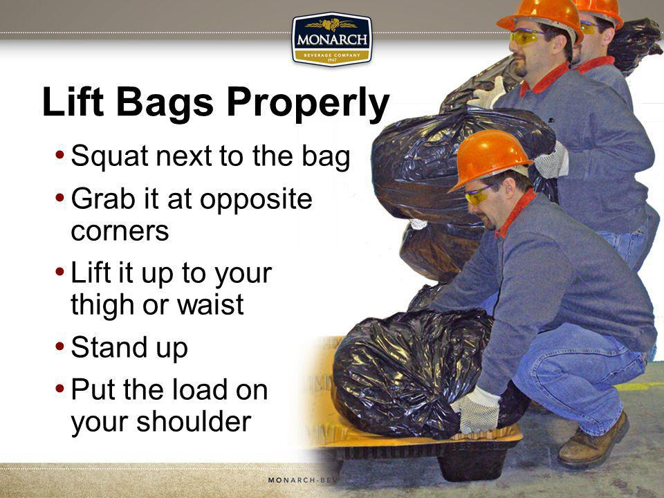 Squat next to the bag Grab it at opposite corners Lift it up to your thigh or waist Stand up Put the load on your shoulder Lift Bags Properly