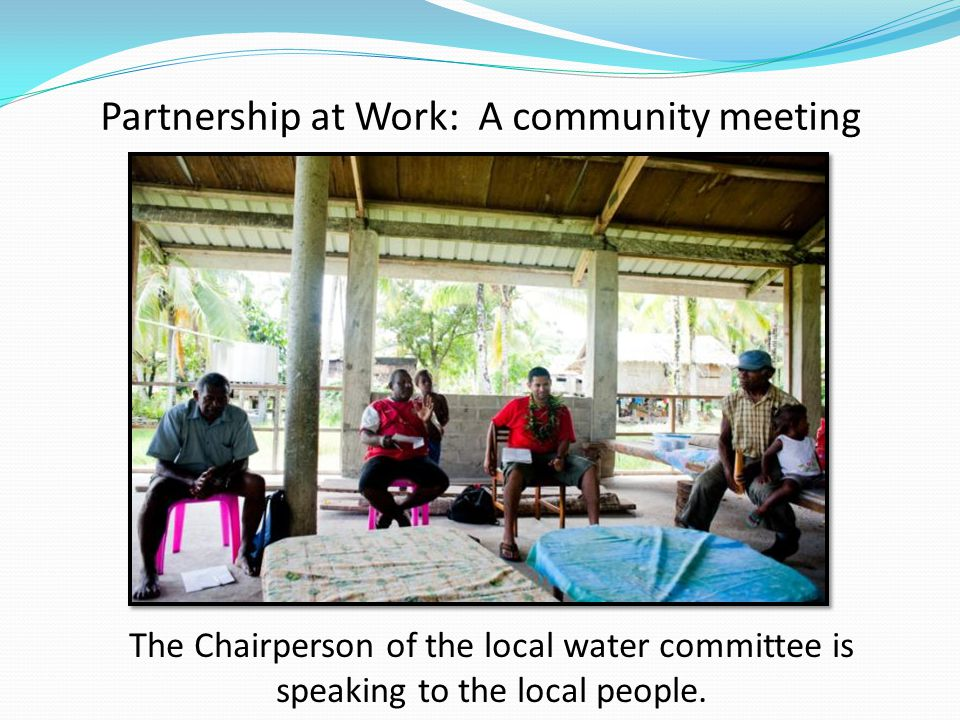 Partnership at Work: A community meeting The Chairperson of the local water committee is speaking to the local people.