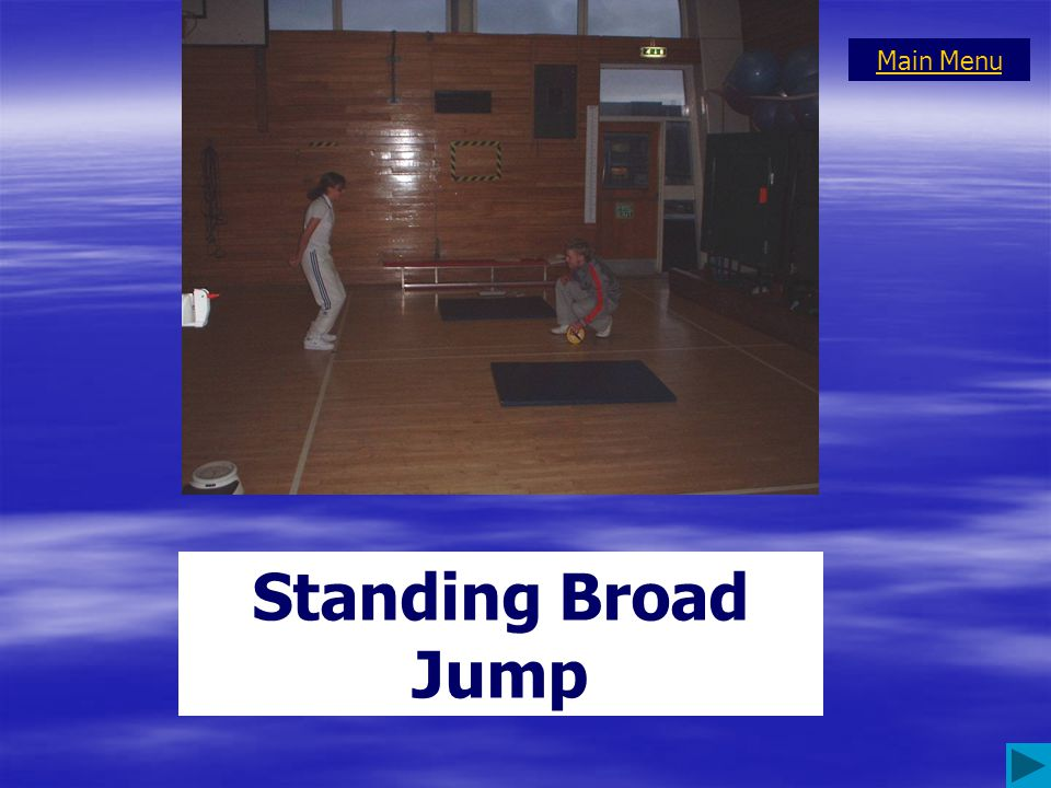 Feet shoulder width apart, toes to the start line. Hands clenched behind the back. Performer is instructed to jump as far forward as possible and to l