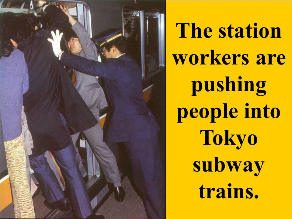 The station workers are pushing people into Tokyo subway trains.