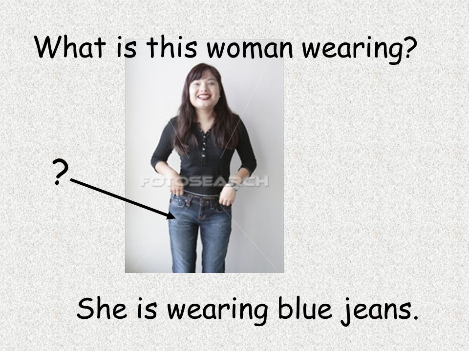 ? She is wearing blue jeans. What is this woman wearing?