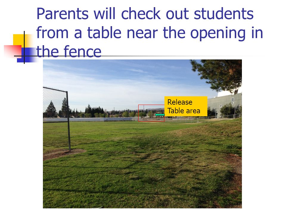 Parents will check out students from a table near the opening in the fence Release Table area