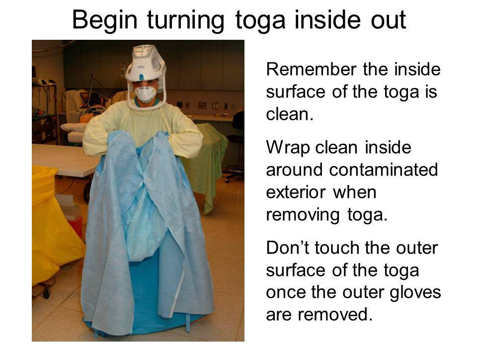 Begin turning toga inside out Remember the inside surface of the toga is clean. Wrap clean inside around contaminated exterior when removing toga. Don