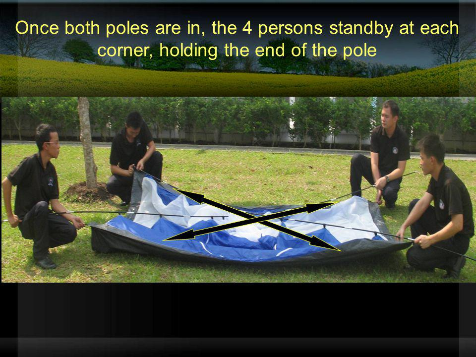 Once both poles are in, the 4 persons standby at each corner, holding the end of the pole