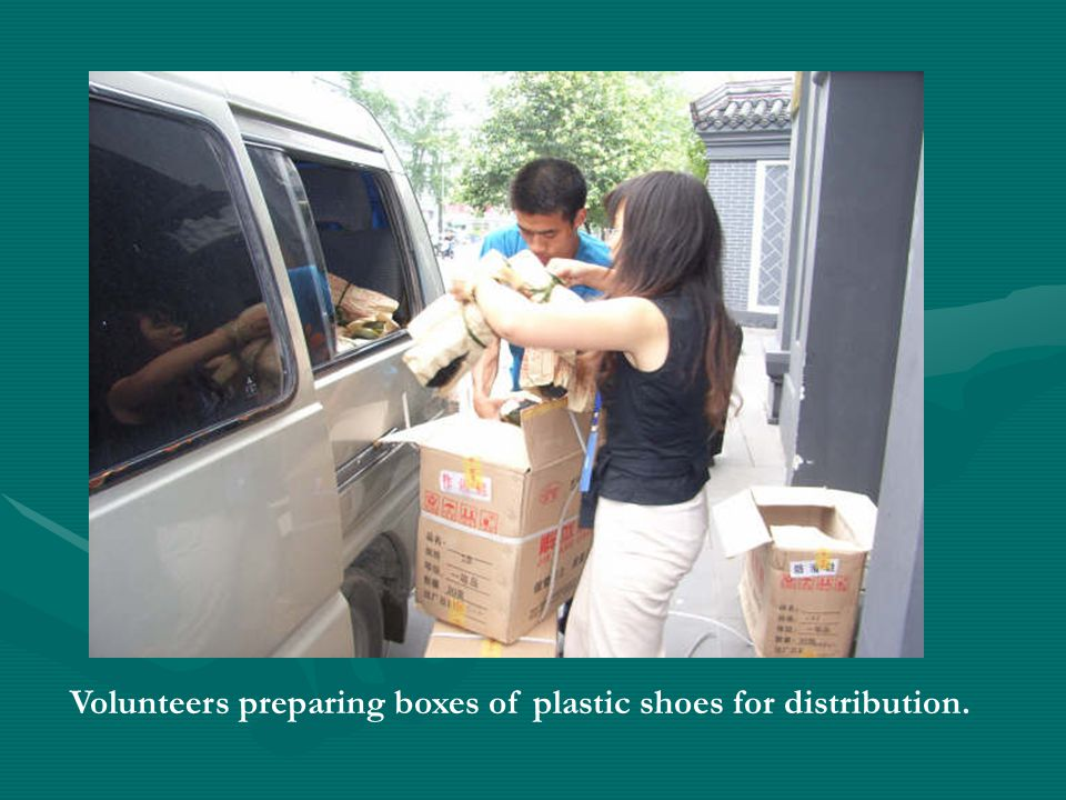 Volunteers preparing boxes of plastic shoes for distribution.