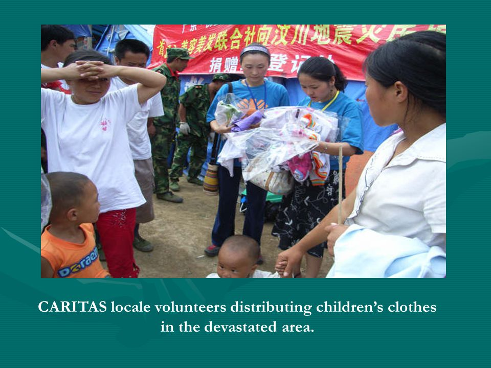 CARITAS locale volunteers distributing childrens clothes in the devastated area.