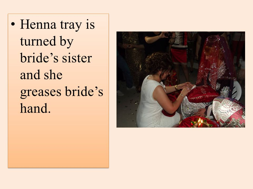 Henna tray is turned by brides sister and she greases brides hand.