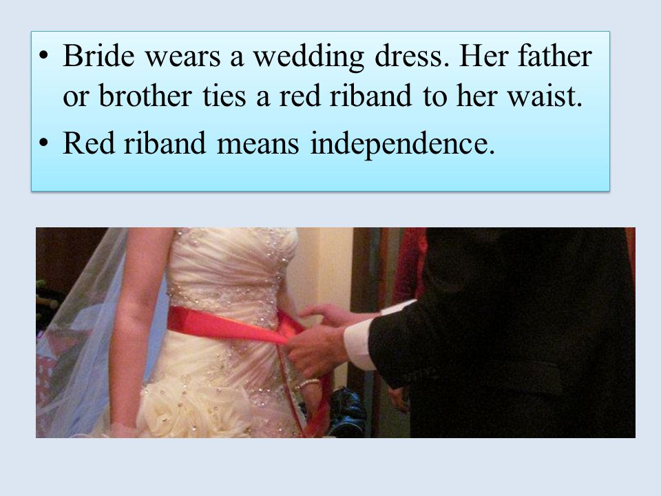 Bride wears a wedding dress. Her father or brother ties a red riband to her waist. Red riband means independence. Bride wears a wedding dress. Her fat