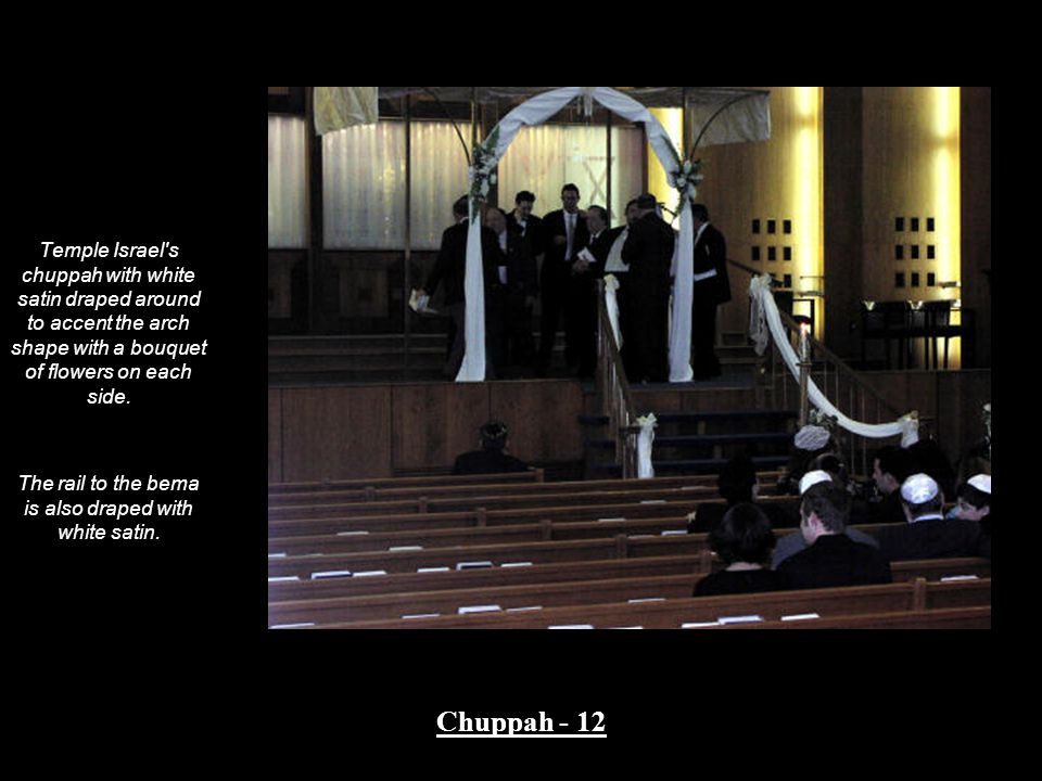 Temple Israel's chuppah with white satin draped around to accent the arch shape with a bouquet of flowers on each side. The rail to the bema is also d