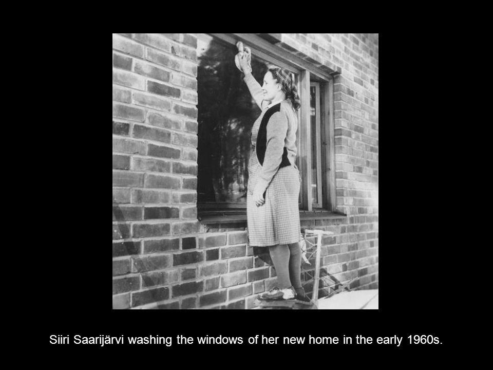 Siiri Saarijärvi washing the windows of her new home in the early 1960s.