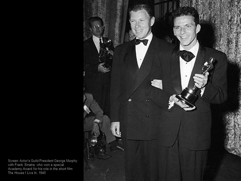 John Wayne, backstage with Howard Hughes, holds two Oscar statuettes; one for Gary Cooper, who won best actor, and one for director John Ford, who won