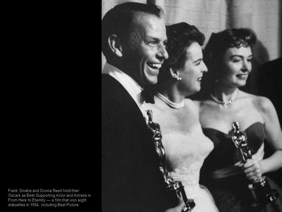 Photographers snap their cameras Oscar winners Ingrid Bergman (Gaslight) and Bing Crosby (Going My Way) at the 1945 Academy Awards.