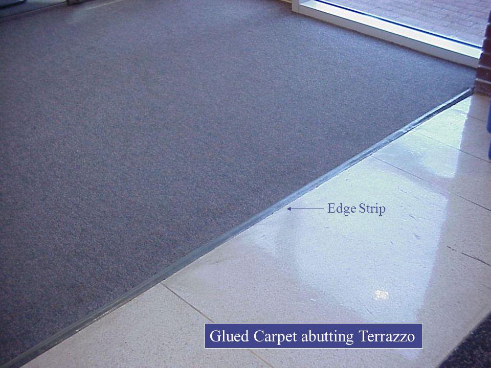 Glued Carpet abutting Terrazzo Edge Strip
