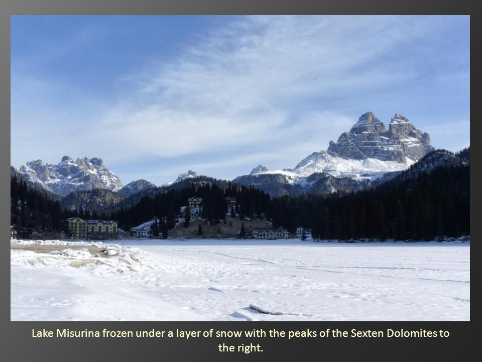 Lake Misurina frozen under a layer of snow with the peaks of the Sexten Dolomites to the right.