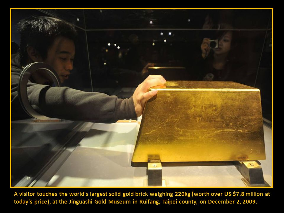 A visitor touches the world s largest solid gold brick weighing 220kg (worth over US $7.8 million at today s price), at the Jinguashi Gold Museum in Ruifang, Taipei county, on December 2, 2009.