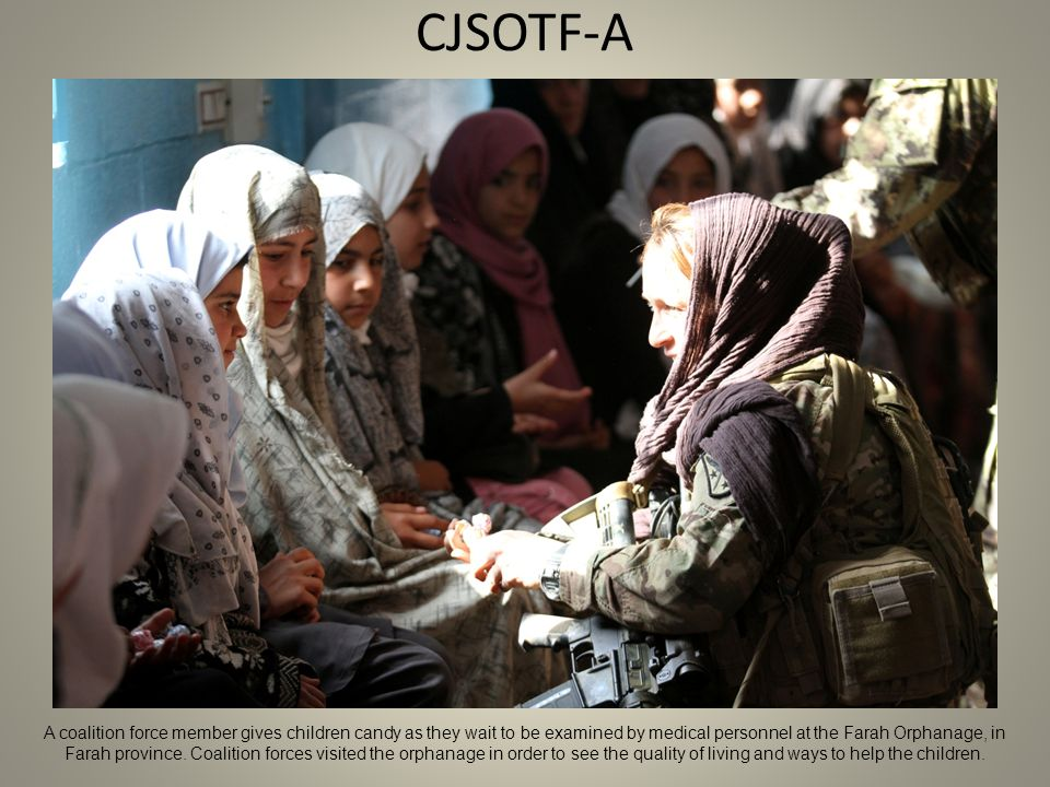 CJSOTF-A A coalition force member gives children candy as they wait to be examined by medical personnel at the Farah Orphanage, in Farah province.