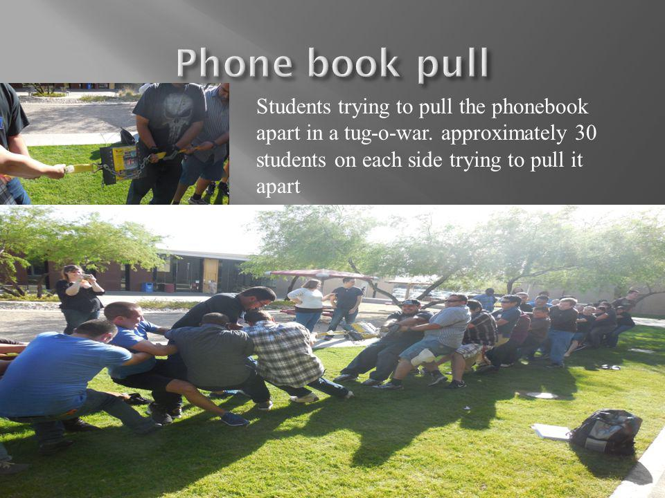 Students trying to pull the phonebook apart in a tug-o-war.